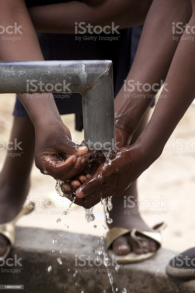 Children washing their hands at a village water pump stock photo