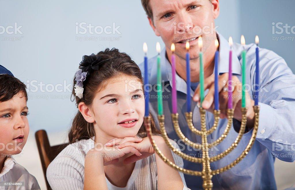 Children watching father light Hanukkah Menorah stock photo