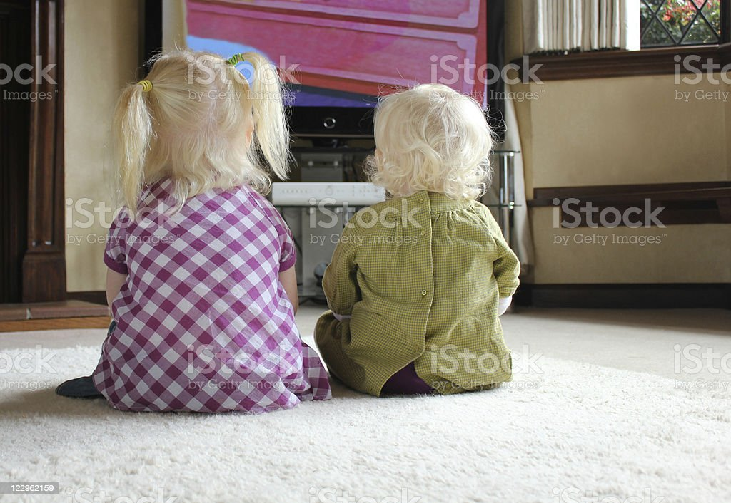children watching television together stock photo