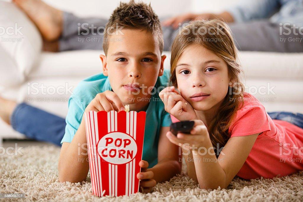 Children watching TV, lying down on the floor stock photo