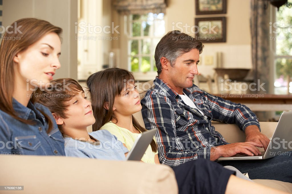 Children Watching TV Whilst Parents Use Laptop stock photo