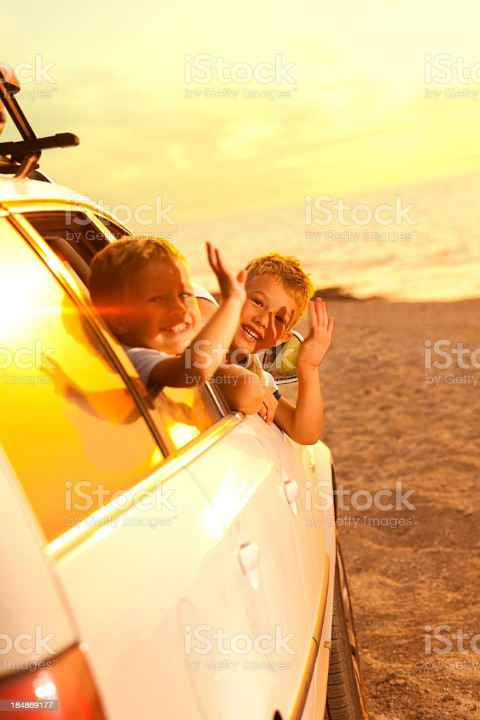 Children waving from car as they arrive at beach royalty-free stock photo