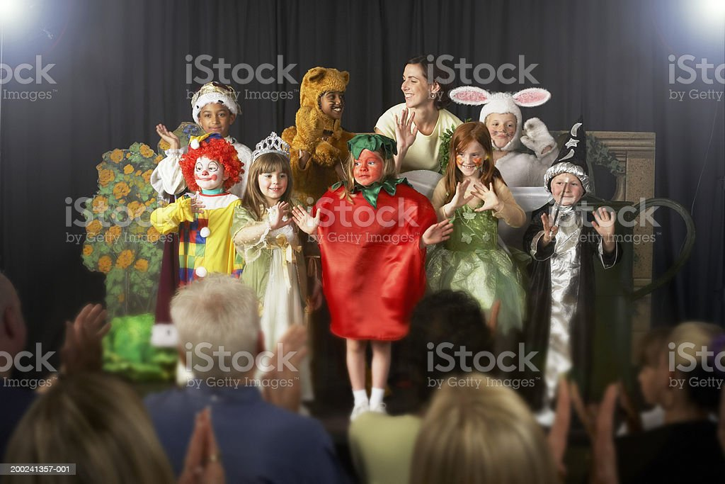 Children (4-9) wearing costumes and teacher waving on stage stock photo
