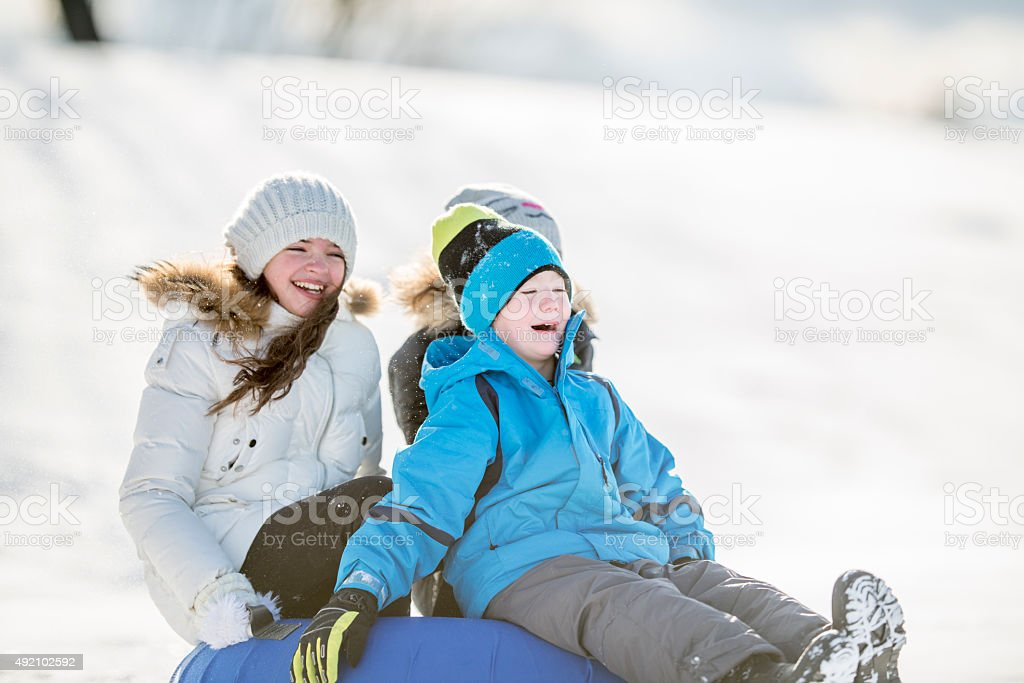 Children Wearing Winter Clothes and Inner Tubing in the Park stock photo