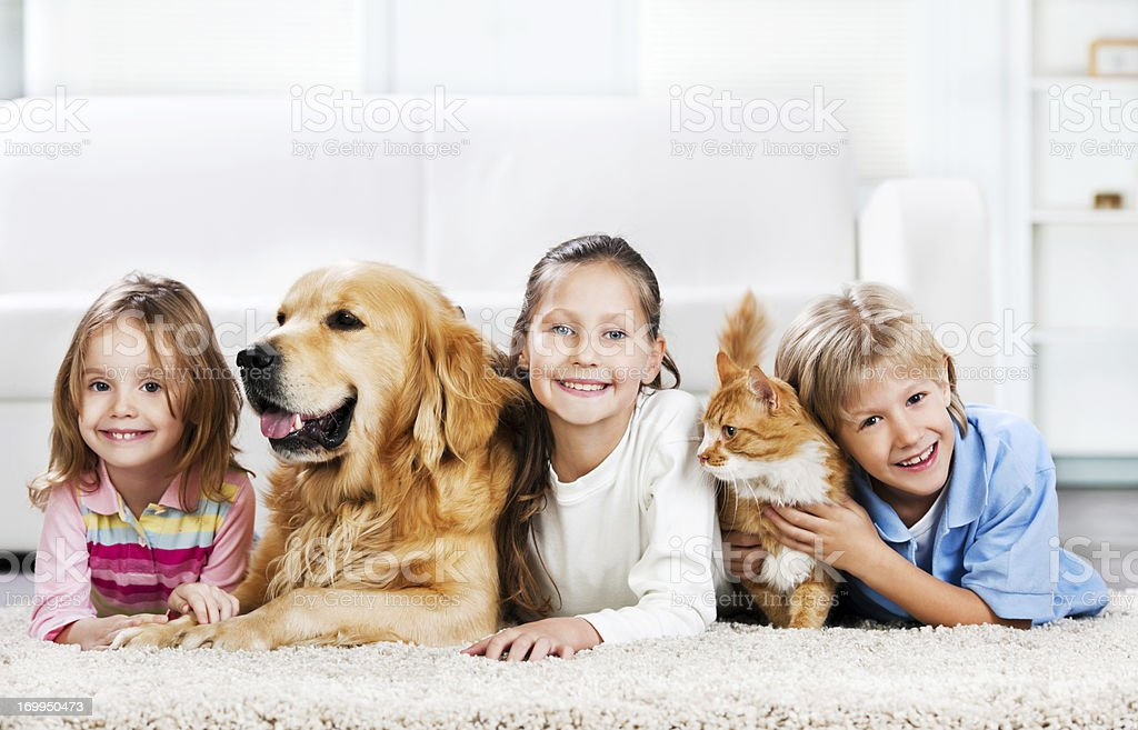 Children with animals lying down on the carpet stock photo