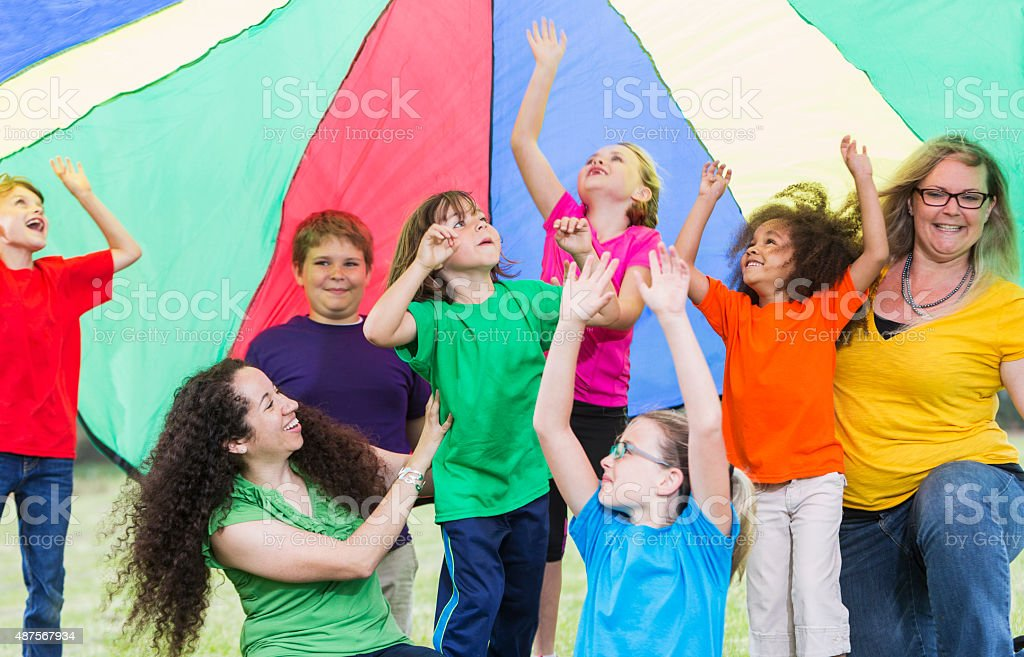 Children with camp counselors under colorful parachute stock photo