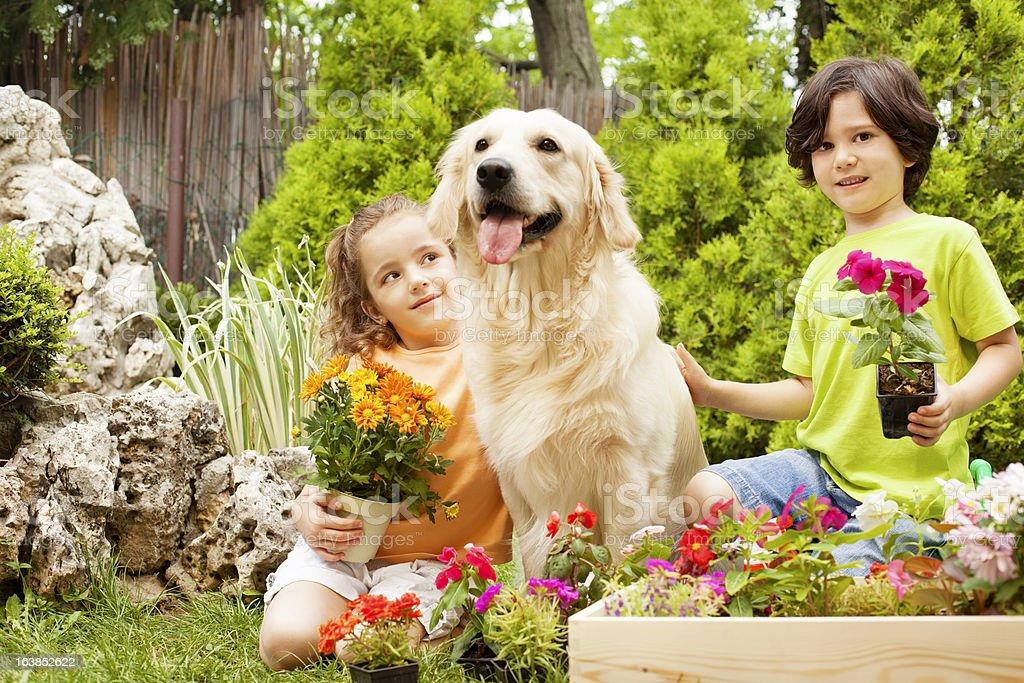 Children with dog gardening. royalty-free stock photo
