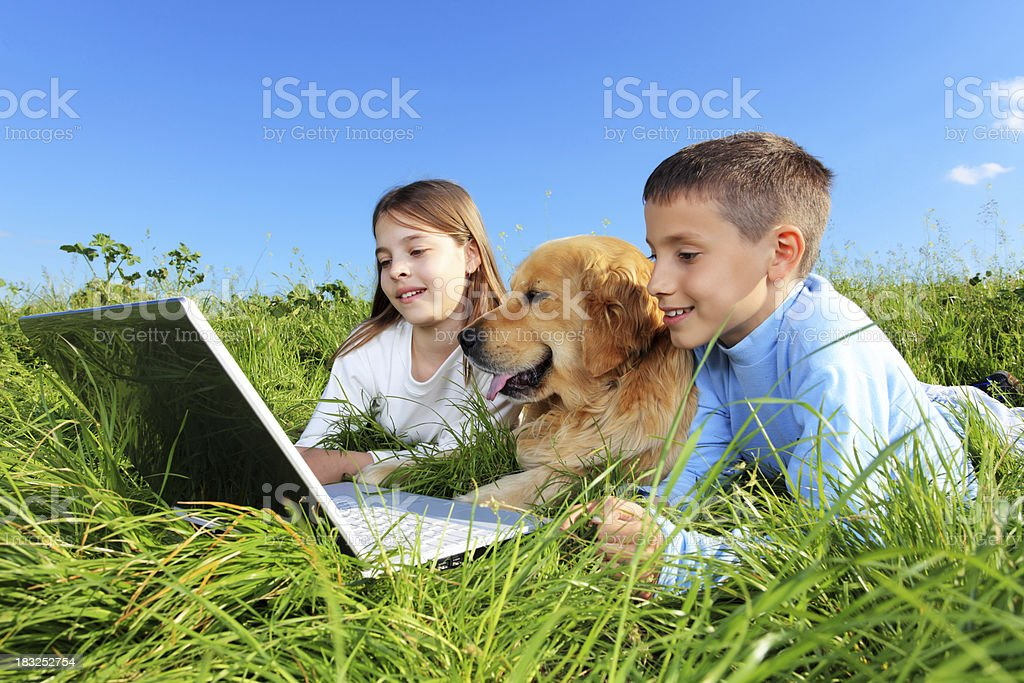 Children with dog resting on meadow and using laptop royalty-free stock photo