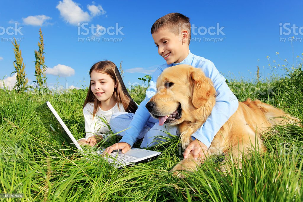 Children with dog resting on meadow. royalty-free stock photo