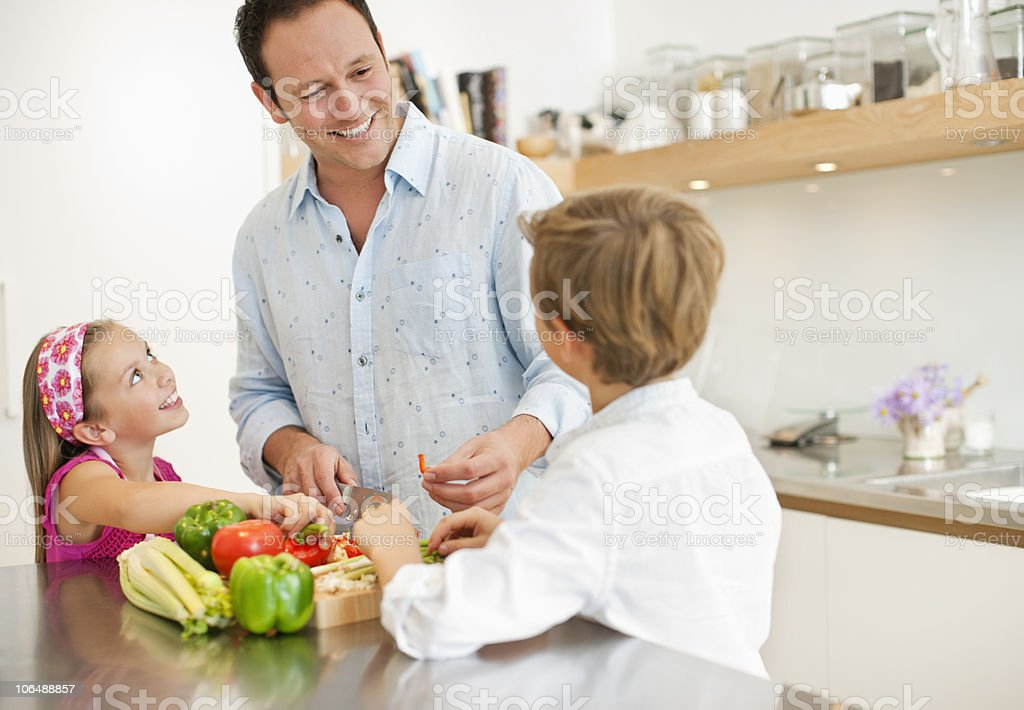 Children (8-11) with father chopping vegetables in kitchen royalty-free stock photo