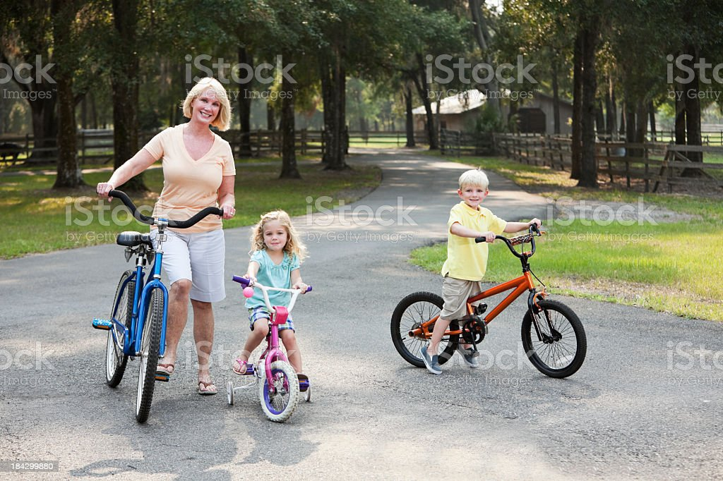 Children with grandmother riding bikes royalty-free stock photo