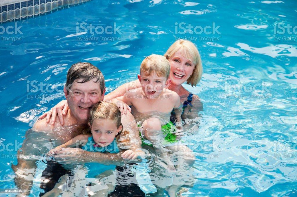 Children with grandparents in swimming pool stock photo