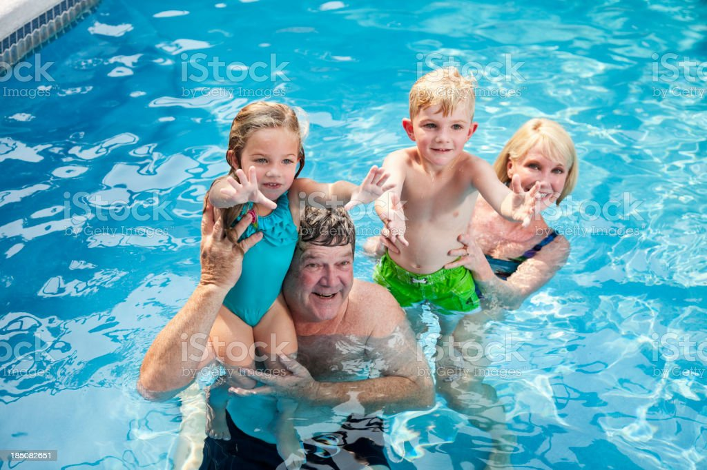 Children with grandparents in swimming pool royalty-free stock photo