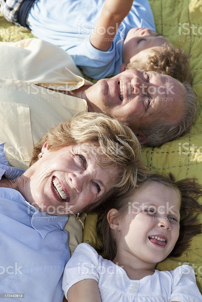 Children with grandparents playing outdoors stock photo
