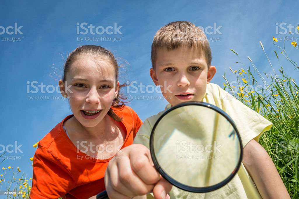 children with magnifying lens exploring the nature outdoors stock photo