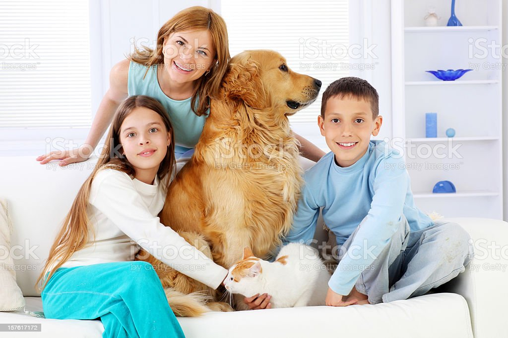 Children with mother and pets sitting on white sofa. royalty-free stock photo
