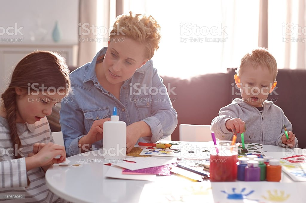 Children with mother painting at home stock photo