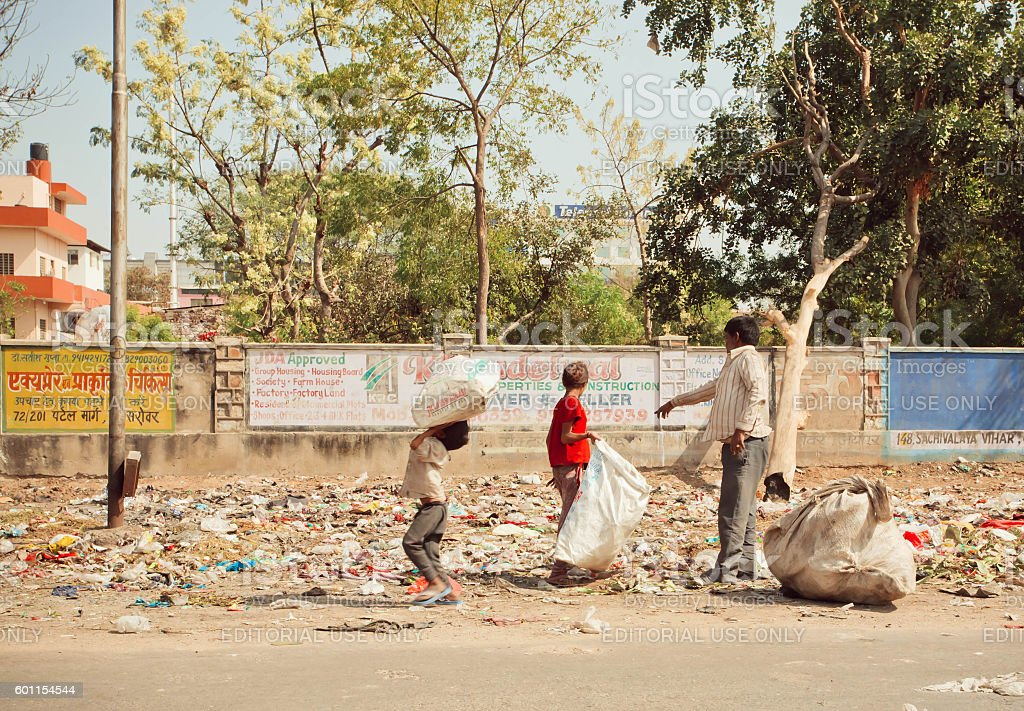 Children with poor father clean out debris for recycling process stock photo