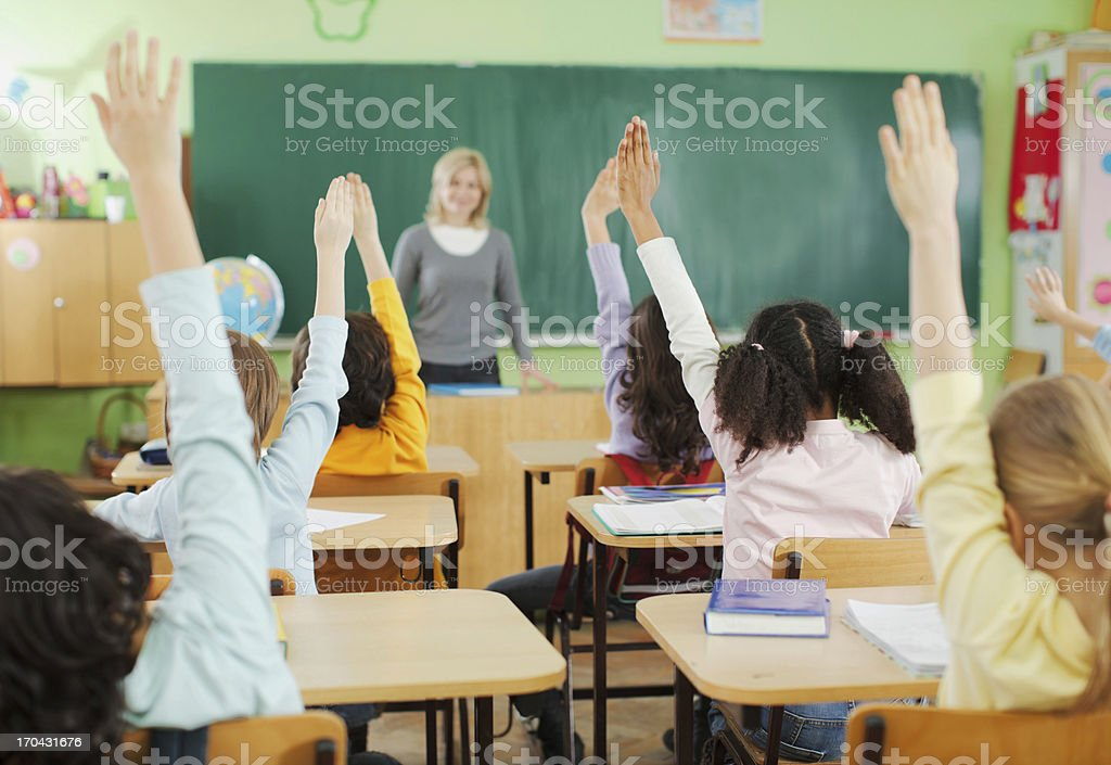 Children with raised hands in classroom royalty-free stock photo