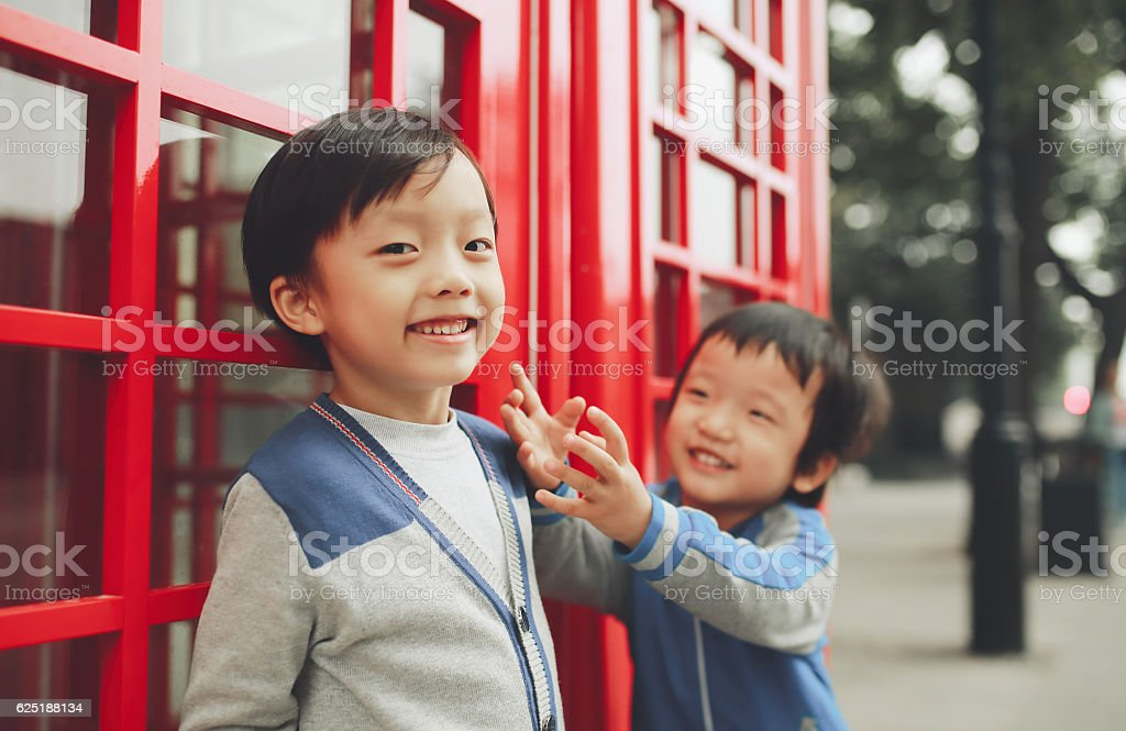 Children with red telephone box in the city stock photo