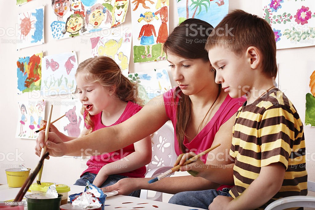 Children with teacher draw paints in play room. royalty-free stock photo