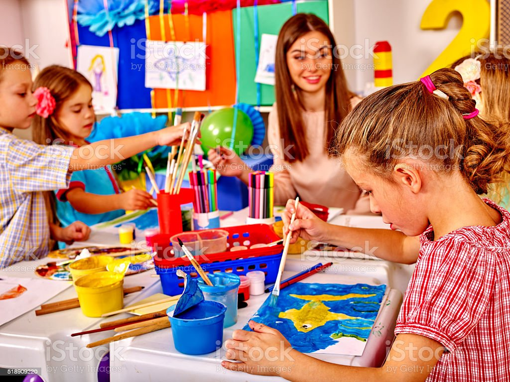 Children with teacher woman painting on paper in  kindergarten stock photo