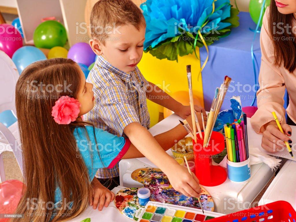 Children with teacher woman painting on paper in  kindergarten . stock photo