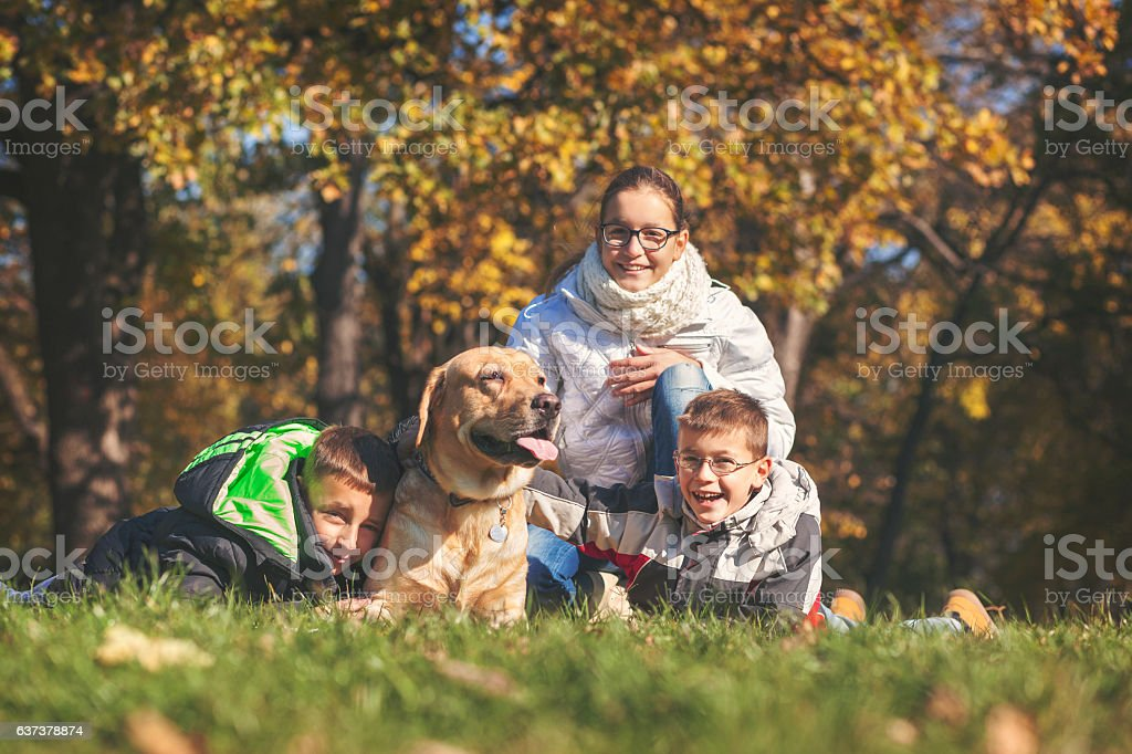 Children with their dog outdoors stock photo
