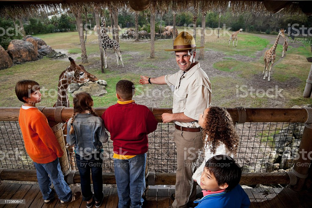 Children with zookeeper at giraffe exhibit stock photo