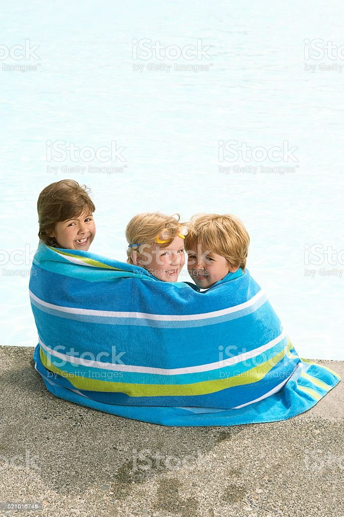 Children wrapped in a beach towel stock photo