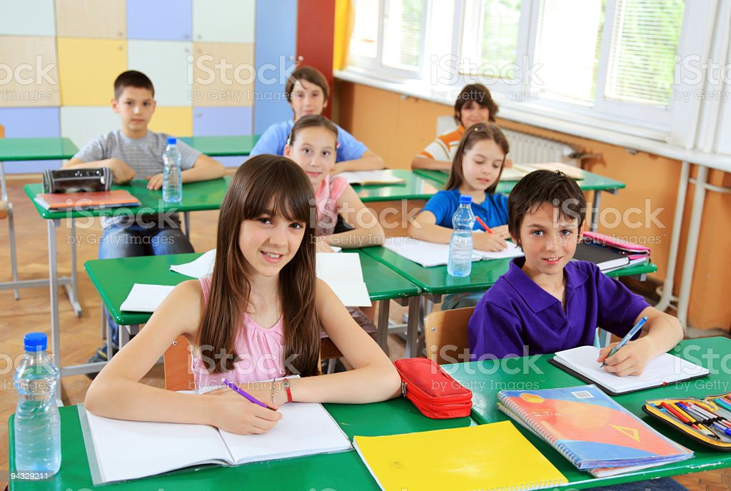 Children writing in notebook on a lesson. stock photo