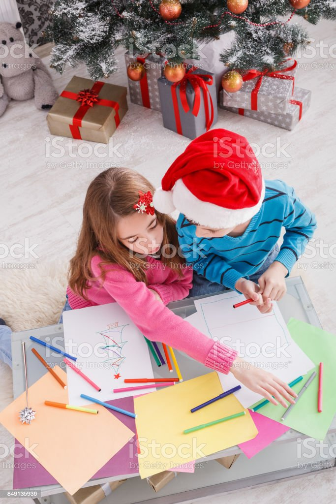 Children writing letter to santa, wait for christmas stock photo