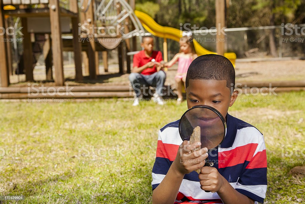 Children:  Young boy using magnifying glass to study nature royalty-free stock photo