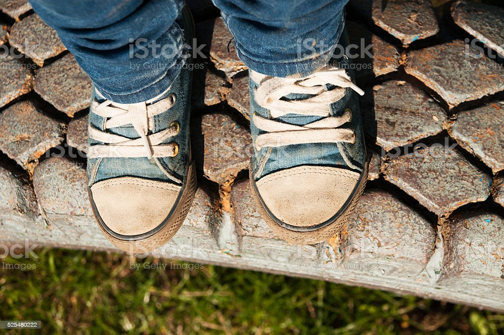children's blue sneakers with jeans on tire stock photo