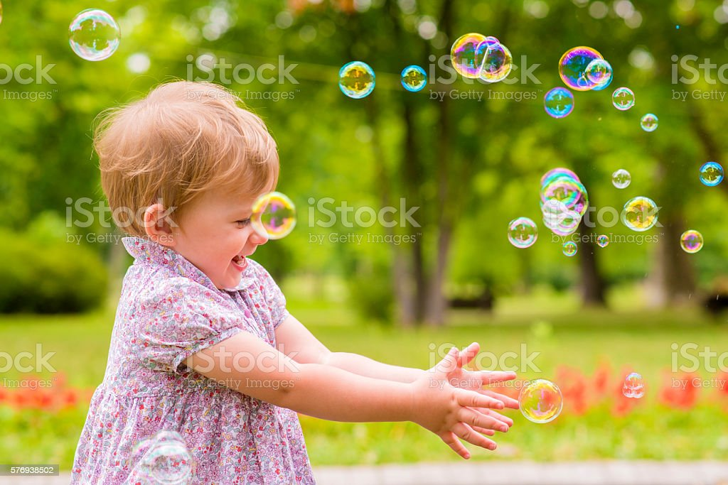 children's entertainment, Child playing with soap bubbles outsid stock photo