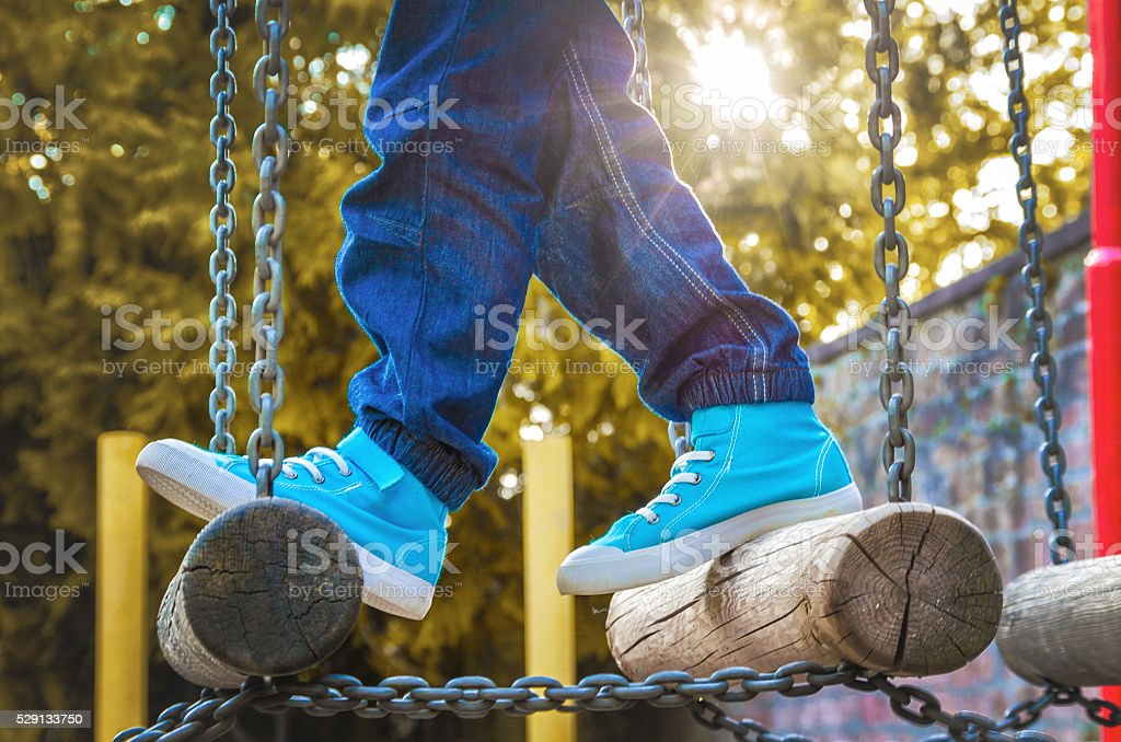 Children's feet in sneakers on the playground with obstacles stock photo