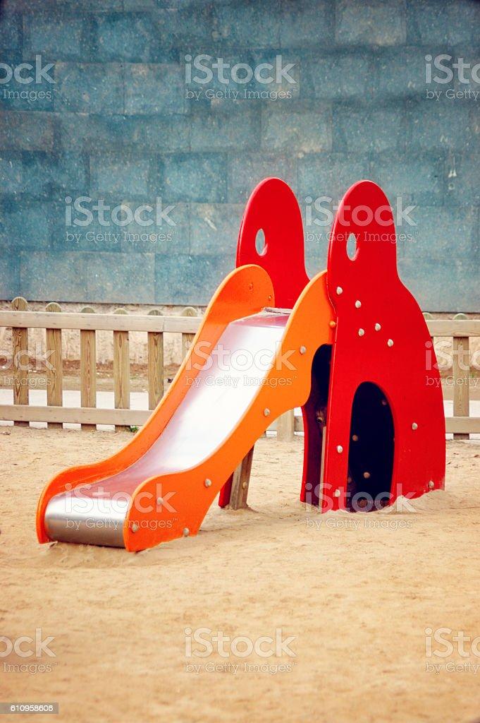 Children's Fenced, Sandy, Playground Slide with Brick Backdrop stock photo