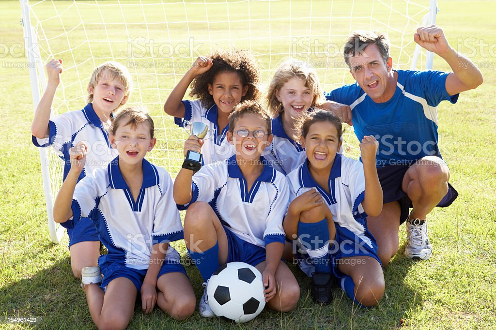 A children's football team celebrating with a trophy stock photo
