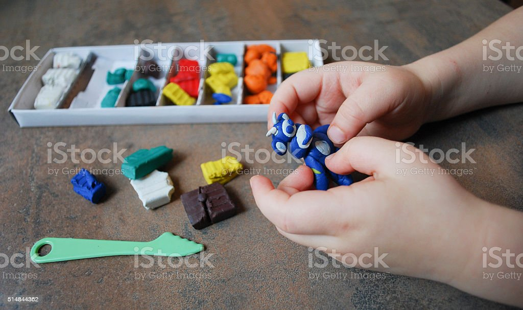 Children's hand holding a figure from Plasticine. stock photo