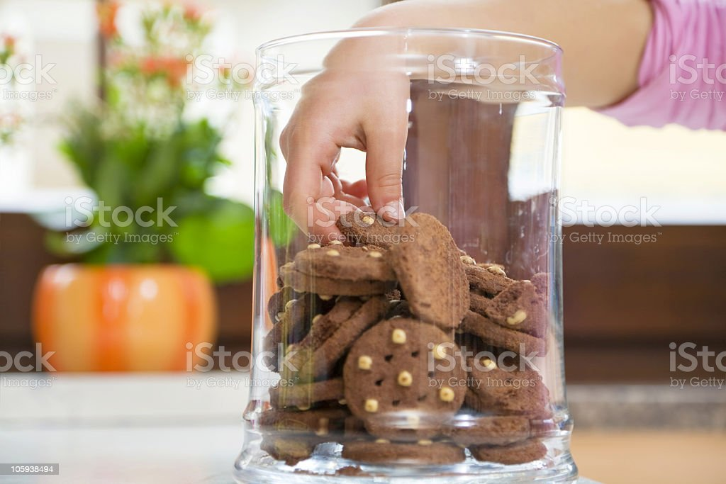 Children's hand in the cookie jar grabbing a cookie stock photo