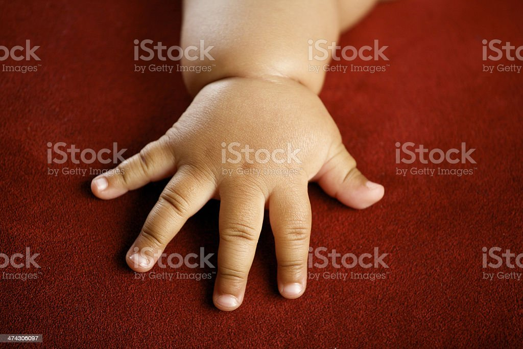 Children's hand isolated on red background stock photo
