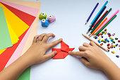 Children's hands do origami  bird from red paper.