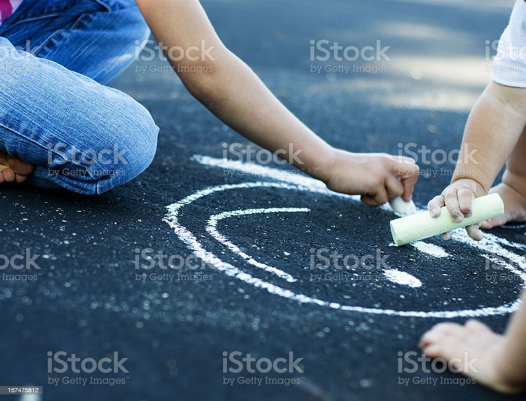 Children's Hands Drawing Picture With Sidewalk Chalk royalty-free stock photo