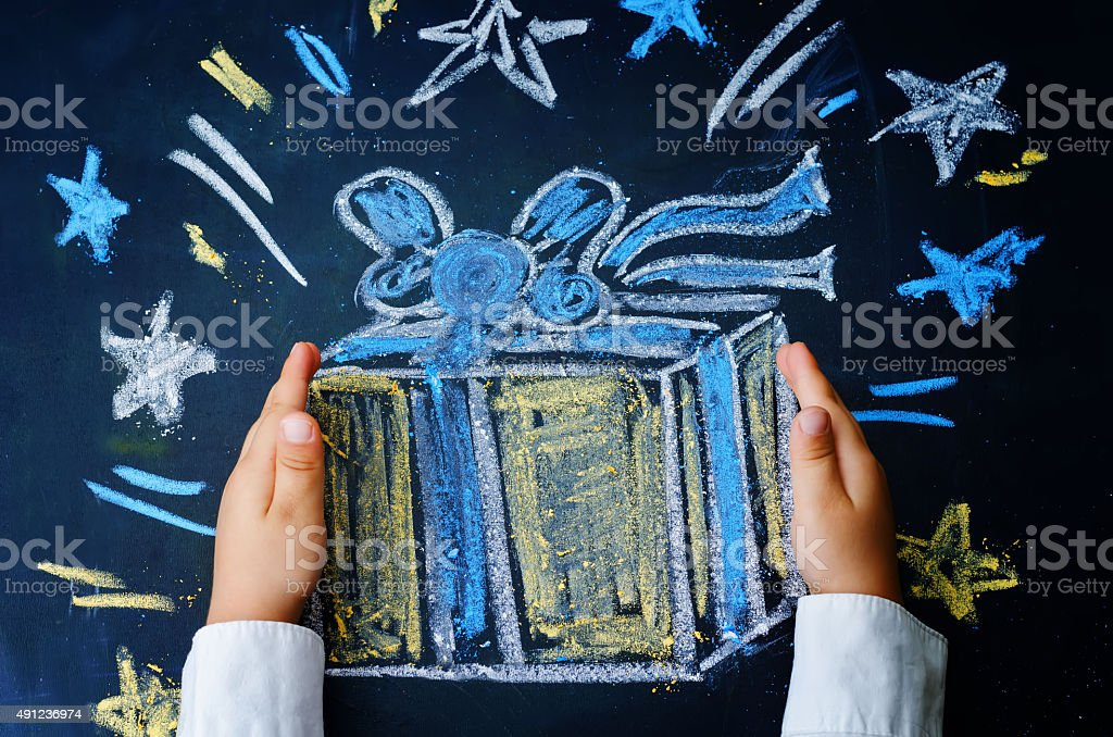childrens hands holding a gift drawn with chalk stock photo