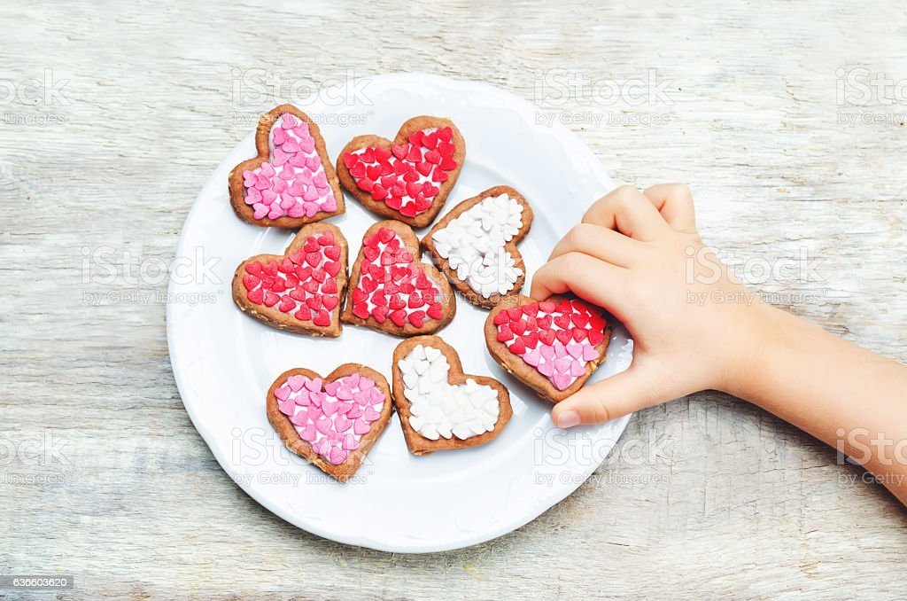 Children's hands holding cookie in the forms of heart stock photo