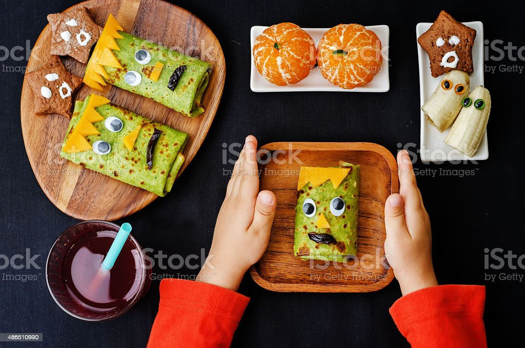 childrens hands holding plate with lunch for Halloween stock photo