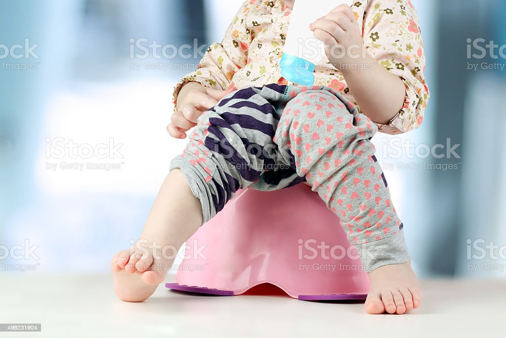 Children's legs hanging down from a chamber-pot on a blue stock photo