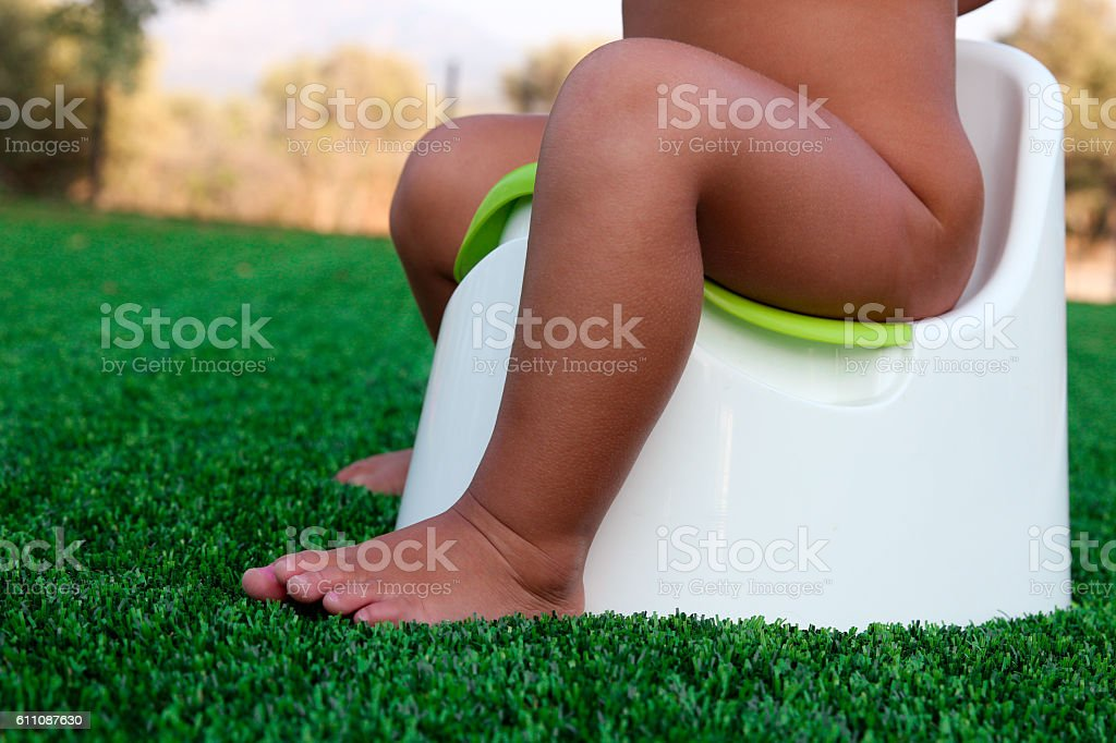 Children's legs hanging down from a chamber-pot on a green stock photo