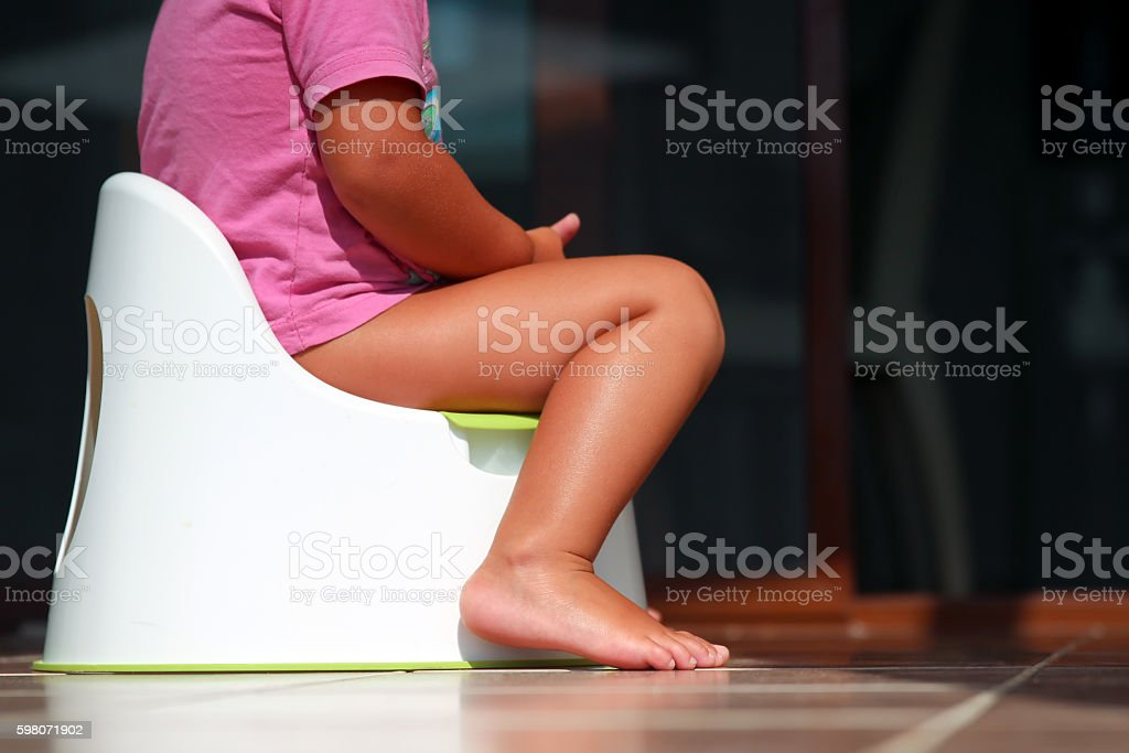 Children's legs hanging down from a chamber-pot stock photo