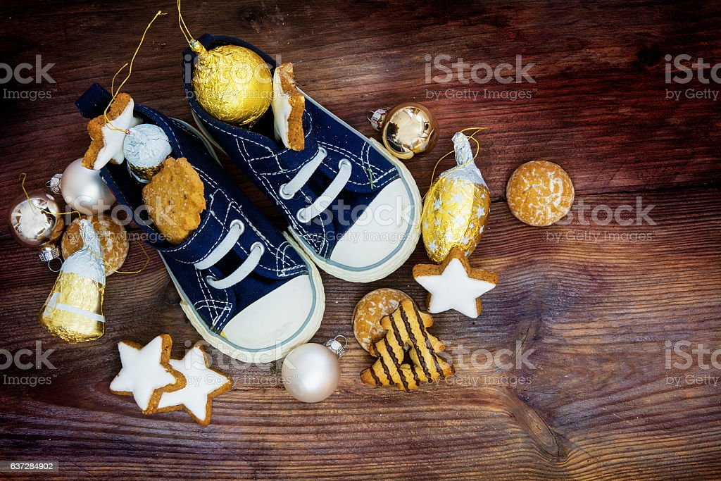 Childrens shoes filled with cookies and christmas decoration stock photo
